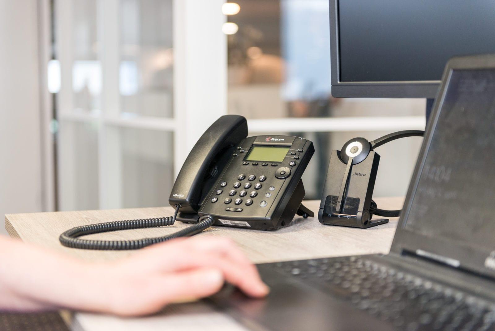 vaste telefoon op werkplek met mobiele telefoon en laptop